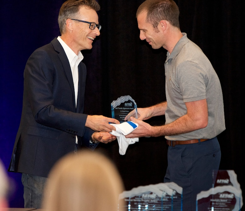 Matt Fetrow, Air Force Research Laboratory Tech Engagement Office director, presents AFRL scientist Dr. Vince Cowan the Tech Transfer Agreement Award at AFRL New Mexico's 2019 Innovation Awards event held on Aug. 9 in Albuquerque, N.M.