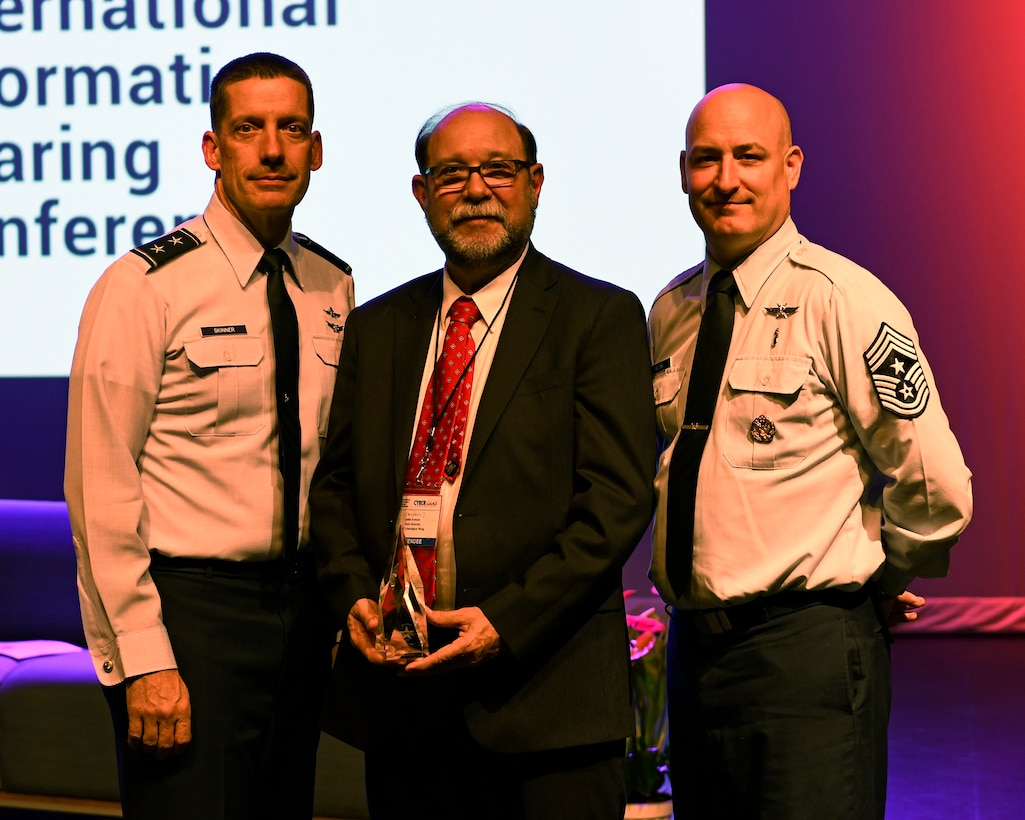 J. Michael Kretzer, 688th Cyberspace Wing technical director, poses for a photo with Maj. Gen. Robert Skinner, 24th Air Force commander, and Chief Master Sgt. David Klink, 24th AF command chief, after being inducted into the CyberTexas Foundation's 2019 Cyber Hall of Honor in San Antonio, Aug. 20, 2019. Kretzer was honored for his nearly 45 years of cybersecurity service to the nation. (U.S. Air Force photo by Tech. Sgt. R.J. Biermann)