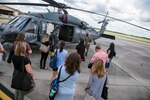 Team Moody spouses observe an HH-60G Pave Hawk helicopter during a Heart Link spouse orientation Aug. 21, 2019, at Moody Air Force Base, Ga. The orientation is geared toward providing all spouses and family members with the necessary support and information to ensure that they are aware of the resources available to them such as: Tricare, legal assistance, Airman and Family Readiness Center and financial assistance. During the orientation, spouses were given a static display tour to better familiarize them with the aircraft and mission here. (U.S. Air Force photo by Airman 1st Class Eugene Oliver)