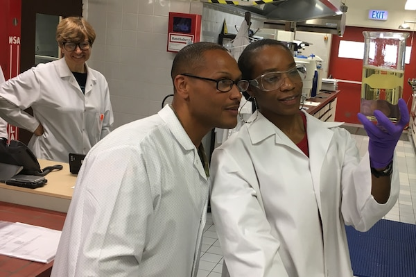 Two individuals inspect a fuel sample.