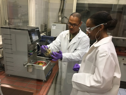 Two people inspect a fuel sample.