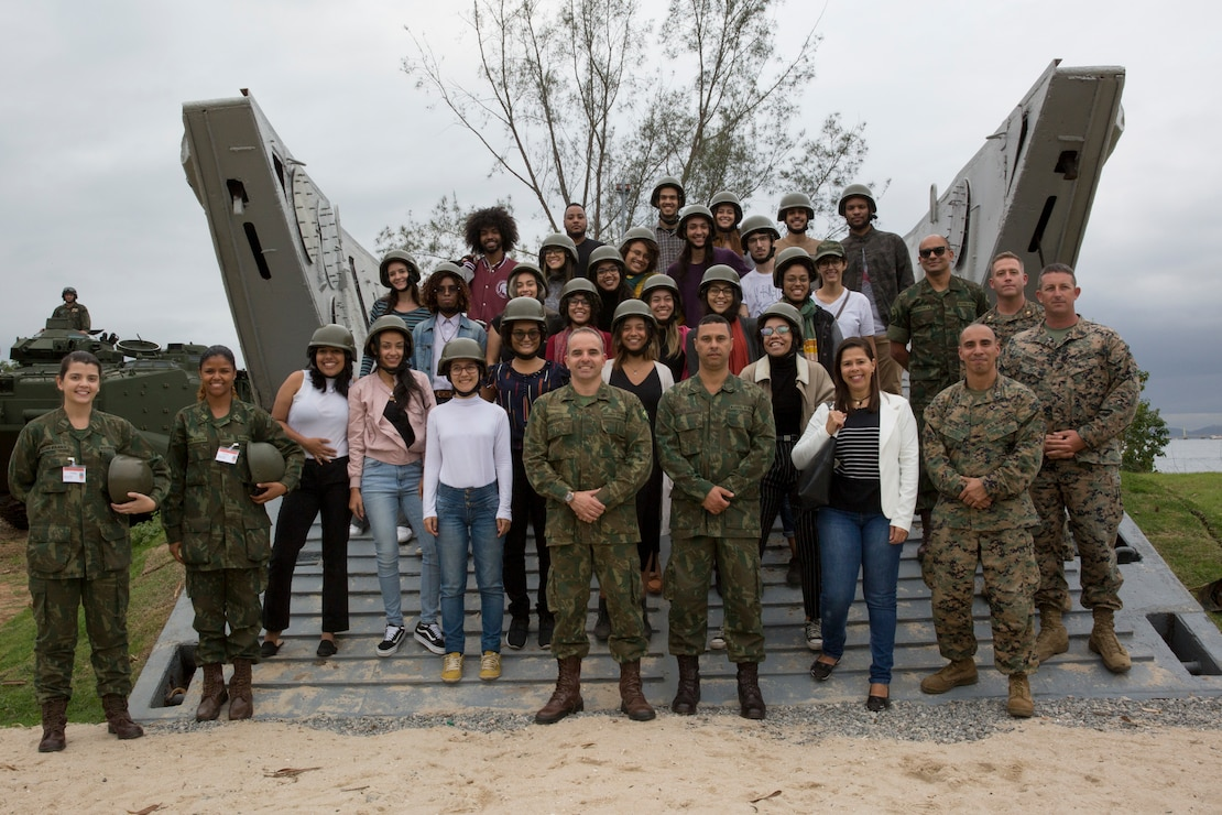 U.S. Marines, Brazilian Marines and students from Universidade Federal do Rio de Janeiro take a group photo during a tour at Ilha do Governador during UNITAS LX, Aug. 21, 2019. UFRJ students toured the base to better understand military capabilities and relations. UNITAS is the world's longest-running, annual exercise and brings together multinational forces from 11 countries to include Brazil, Colombia, Peru, Chile, Argentina, Ecuador, Panama, Paraguay, Mexico, Great Britain and the United States. The exercise focuses in strengthening the existing regional partnerships and encourages establishing new relationships through the exchange of maritime mission-focused knowledge and expertise during multinational training operations.