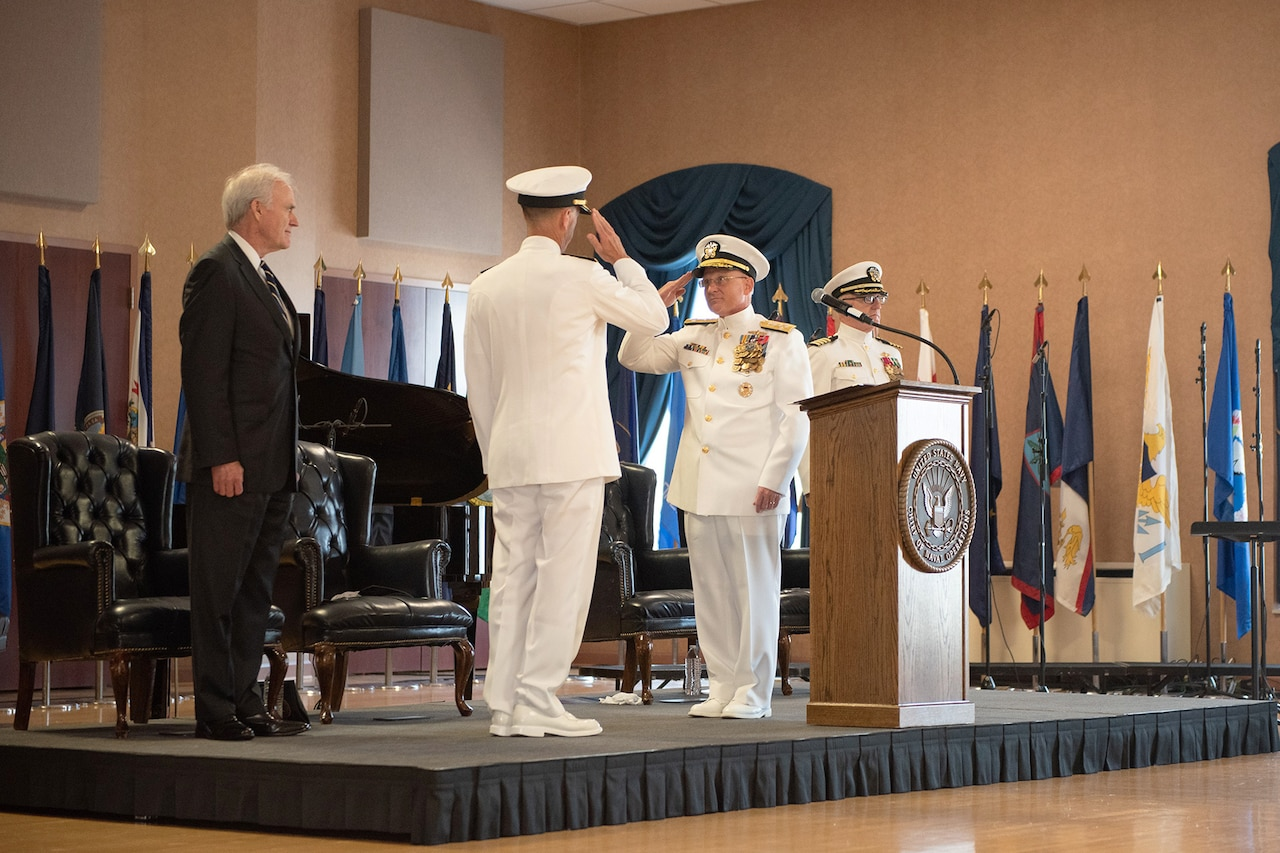 Outgoing and incoming chiefs of naval operations salute.