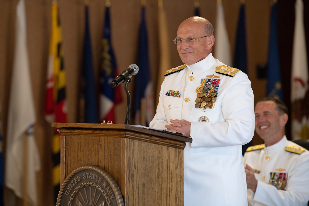 Admiral in white dress uniform speaks at a lectern.