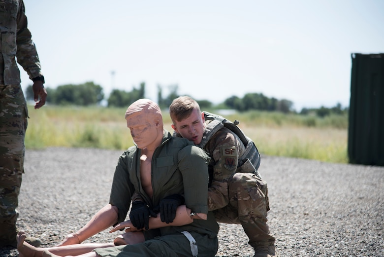 U.S. Air Force A1C Jacob Bailey, 366th Security Forces Squadron response force leader, picks up a body dummy August 16, 2019, at the off-base small arms range near Mountain Home Air Force Base, Idaho. The candidates must complete a 50 meter walk while carrying a 175 pound training dummy. (U.S. Air Force photo by Airman Natalie Rubenak)