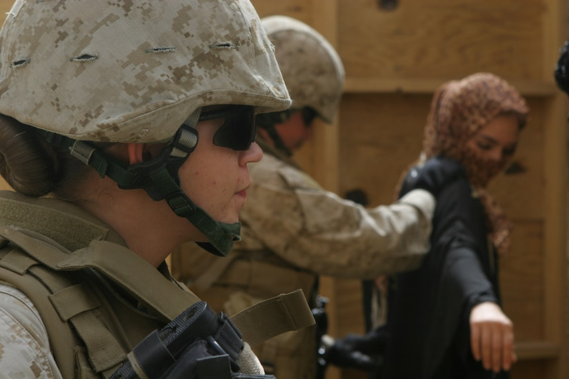 A Marine in combat equipment stands in the foreground as another Marine searches a role-playing civilian.