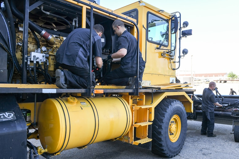 (Left to right) Airman Sean Horwath, Airman 1st Class Jason Owens, and Senior Airman Jacob Wilcox, 75th Logistics Readiness Squadron, perform maintenance on an OshKosh snow broom at Hill Air Force Base, Utah, Aug. 1, 2019. The squadron is overhauling the base's snow fleet after a snowy winter to be ready for the next winter season. (U.S. Air Force photo by Cynthia Griggs)