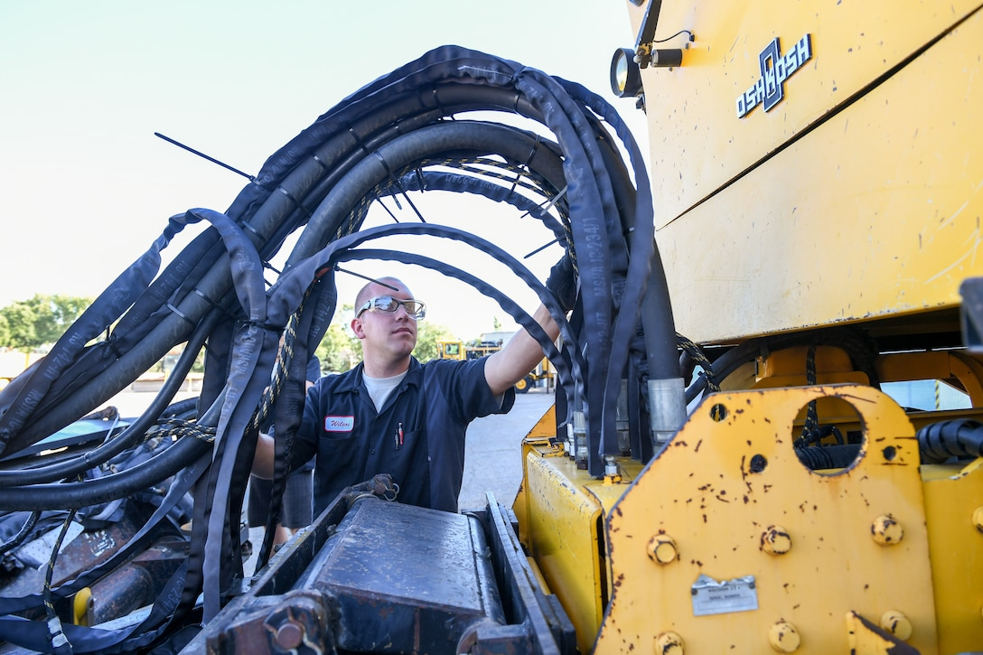 Senior Airman Jacob Wilcox, 75th Logistics Readiness Squadron, performs maintenance on the hydraulics of an OshKosh snow broom at Hill Air Force Base, Utah, Aug. 1, 2019. The squadron is overhauling the base's snow fleet after a snowy winter to be ready for the next winter season. (U.S. Air Force photo by Cynthia Griggs)