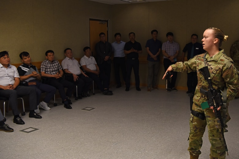 U.S. Air Force Senior Airman Katelynn Hagadorn, 8th Security Forces Squadron multiple interactive learning objectives trainer, showcases an M-9 handgun to Korean National Police Gunsan City branch members at Kunsan Air Base, Republic of Korea, Aug. 20, 2019. Hagadorn showcased the equipment security forces uses on a virtual reality training simulator. (U.S. Air Force photo by Staff Sgt. Joshua Edwards)