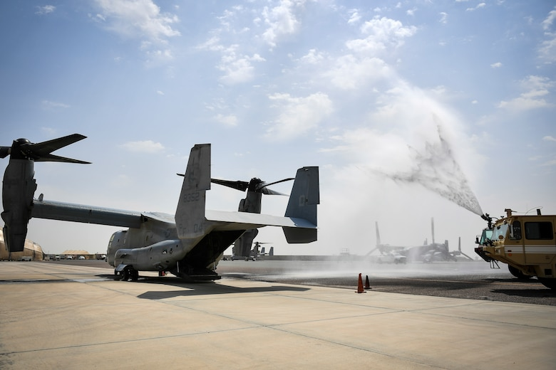 Firefighters from the 407th Expeditionary Civil Engineer Squadron spray a MV-22 Osprey with water during an airfield exercise at Ahmed al-Jaber Air Base, Kuwait, Aug. 16, 2019. The exercise was an opportunity for service members from multiple branches to cooperate on one of the most intense scenarios a firefighter could be called for: an aircraft on fire on the flightline. (U.S. Air Force photo by Staff Sgt. Mozer O. Da Cunha)
