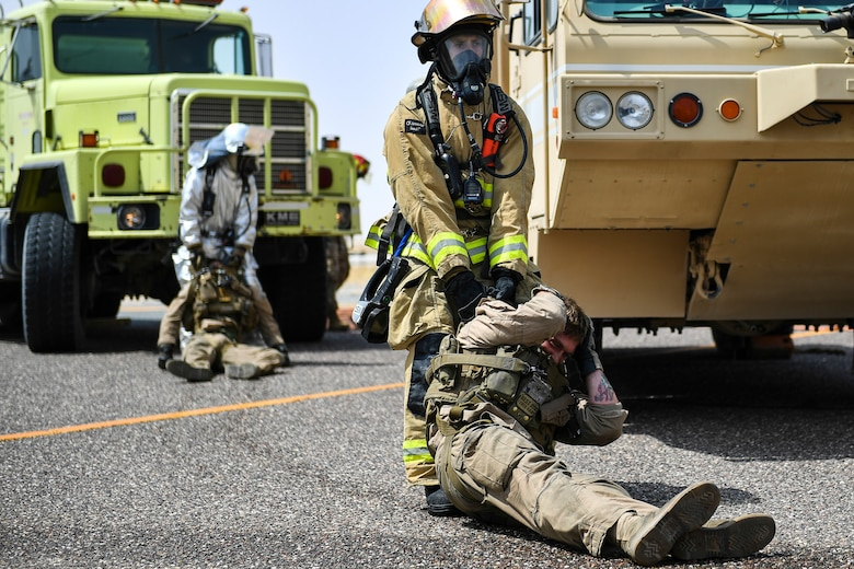 A firefighter with the 407th Expeditionary Civil Engineer Squadron removes a simulated casualty from an MV-22 Osprey during an airfield exercise at Ahmed al-Jaber Air Base, Kuwait, Aug. 16, 2019. The exercise was an opportunity for service members from multiple branches to cooperate on one of the most intense scenarios a firefighter could be called for: an aircraft on fire on the flightline. (U.S. Air Force photo by Staff Sgt. Mozer O. Da Cunha)