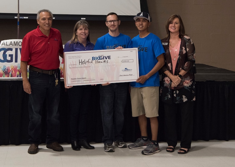 Members of team Helpful Hawks accept a check for winning the people's choice category as part of the 2019 Alamo's Big Give closing ceremony, August 22, at the Willie Estrada Civic Center in Alamogordo, N.M. This was the 12th year of Alamo's Big Give which has saved the Otero community over $2,000,000 through community service. (U.S. Air Force photo by Staff Sgt. BreeAnn Sachs)