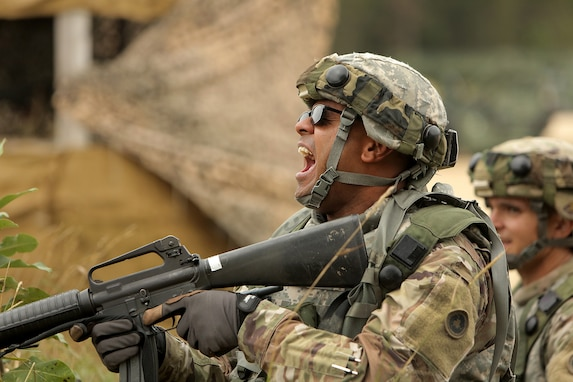 Army Reserve Staff Sgt. Nitendra Prasad, Platoon Sergeant, 645th Inland Cargo Transfer Company, Las Vegas, Nevada, yells at his Soldiers to get down as Civilians on the Battlefield approach an entry control point of the Central Receiving Shipping Point yard during a training scenario involving civilians, August 18, 2019 at Combat Support Training Exercise 86-19-04 at Fort McCoy, Wisconsin.