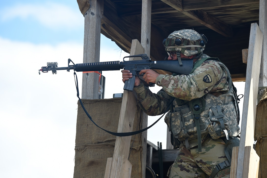 Spc. Dimitri Persad, Motor Transportation Operations Specialist, 211th Inland Cargo Transfer Company, Garden Grove, California, fires at the enemy from a guard tower during a day time attack on August 18, 2019.