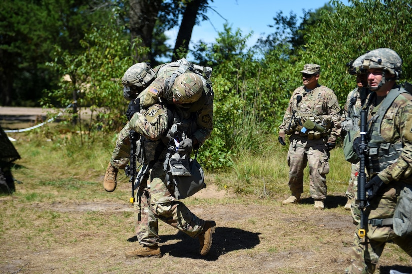 A Soldier assigned to the 143rd Sustainment Command carries a mock injured Soldier to a first aid station for medical treatment after an attack at Combat Support Training Exercise 86-19-04 conducted at Fort McCoy, Wisconsin.
