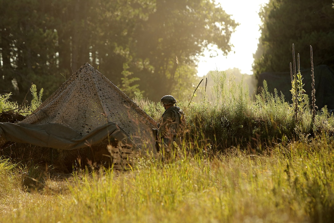 An Army Reserve Soldier stands watch in his fighting position during Stand-To, a state of readiness assumed by Soldiers at dusk and dawn during war, August 20, 2019.