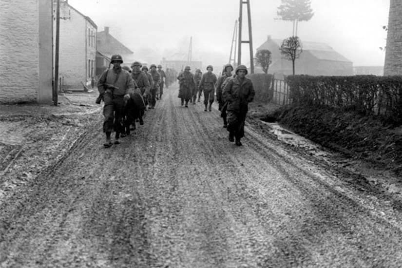 Soldiers in lines of two march down a muddy street. In the background are houses, a tree and several poles.
