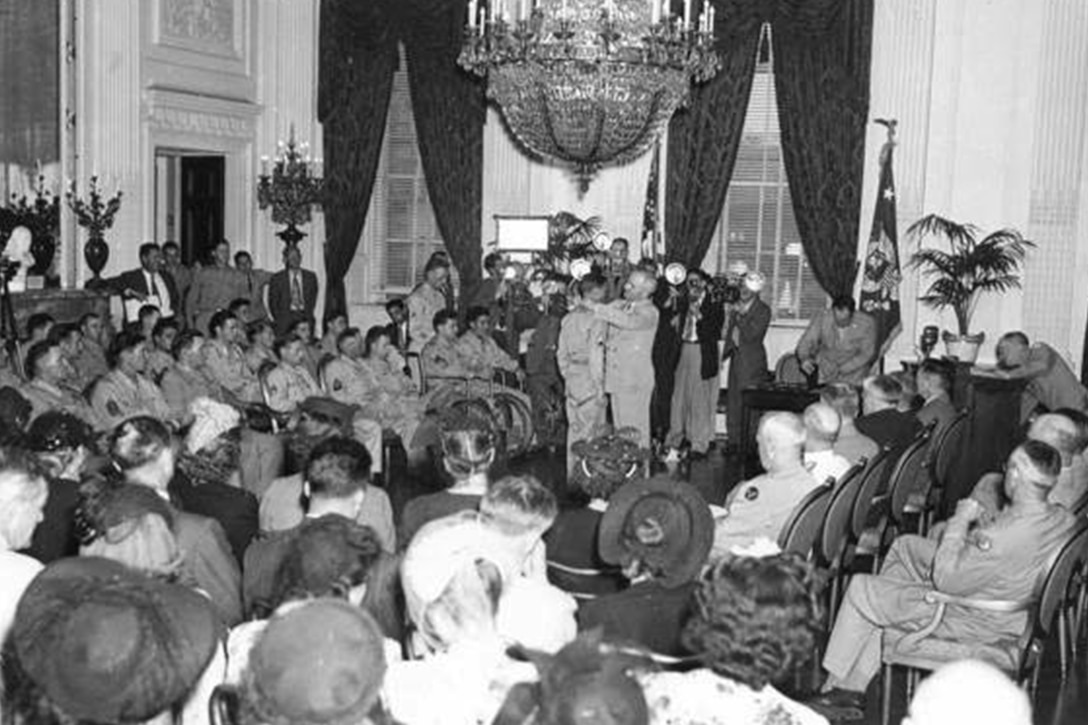 In a room with high ceilings, two curtained windows and a chandelier, a man places a medal around a soldier's neck. Several other soldiers and civilians watch, seated.