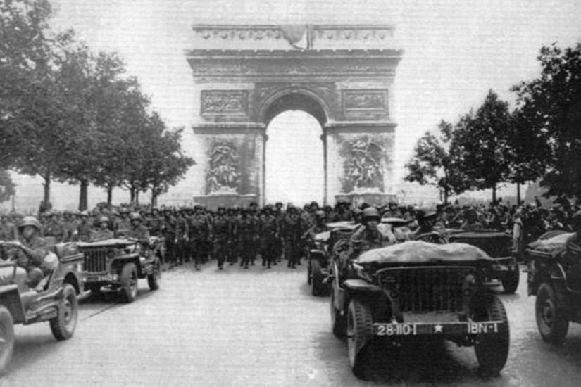 Five Army vehicles drive down a tree-lined street, with hundreds of soldiers marching behind them. In the background is the famed Parisian Arc de Triumphe.