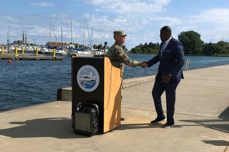 Col. Aaron Reisinger, commander and district engineer of the U.S. Army Corps of Engineers Chicago District, shakes hands with Sam Cunningham, mayor of Waukegan, Illinois, during a ribbon cutting ceremony hosted by the Waukegan Harbor and Marina to reopen the Waukegan South Pier for public use Aug. 22. The Corps removed deteriorated concrete, placed new concrete and added nine new access ladders. (U.S. Army photo by Christina Eddleman/Released)