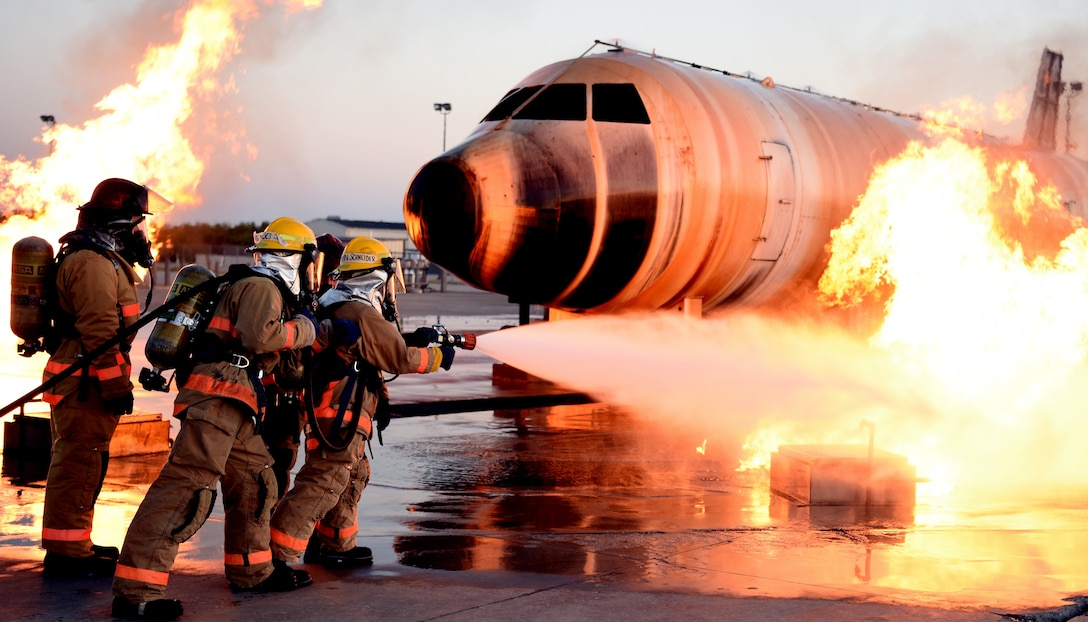 Airman approaches an exterior aircraft fire with water hose