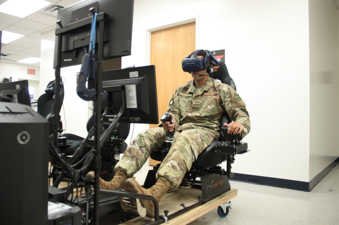 """U.S. Air Force 2nd Lt. Isaac Perez flies a training sortie on a virtual reality simulator at Air Education and Training Command's Detachment 24 on Joint Base San Antonio-Randolph Aug. 20, 2019. Perez, who is awaiting the start of version three of """"Pilot Training Next,"""" was the 2019 winner of the Intercollegiate Tennis Association's national Arthur Ashe Jr. Leadership and Sportsmanship award. (U.S. Air Force photo by 2nd Lt. Robert Guest)"""