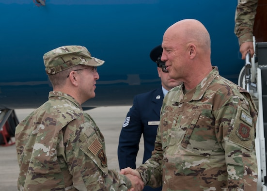 Two people greeting one another on a flightline.
