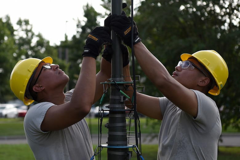 U.S. Air Force Airmen 1st Class Erlin Hernandez and Samuel Sein, 338th Training Squadron Radio Frequency Transmission Systems students, set up an ultra high frequency antenna outside of Jones Hall on Keesler Air Force Base, Mississippi, August 12, 2019. The course has been transitioning to an active learning approach where students teach their peers the course material while an instructor monitors. (U.S. Air Force photo by Senior Airman Suzie Plotnikov)