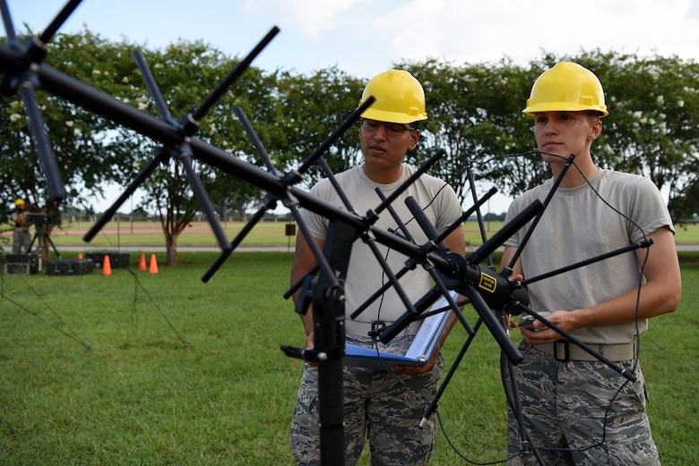 U.S. Air Force Airmen Noah Ruiz and Dante Wolfinger, 338th Training Squadron Radio Frequency Transmission Systems students, set up tactical satellite communication outside of Jones Hall on Keesler Air Force Base, Mississippi, August 12, 2019. The RF Transmission System course is a 653 hour course where students learn line-of-sight communication, high frequency operations, satellite communications and systems and more. (U.S. Air Force photo by Senior Airman Suzie Plotnikov)