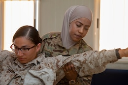 Madaba resident Pvt. Hanady Al-Shakhatreh (right), with Jordan Armed Forces-Arab Army Quick Reaction Force Female Engagement Team (FET), practices physical search procedures on U.S. Marine Corps Sgt. Maricela Tinocoromero, with 11th Marine Expeditionary Unit FET, during detainee operations and handling training August 5, 2019 in Jordan. The U.S. is committed to the security of Jordan and to partnering closely with JAF to meet common security challenges.
