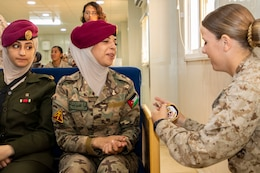 Jordan Armed Forces-Arab Army Quick Reaction Force (FET) member (left) smiles in surprise as U.S. Marine Cpl. Danielle Grimshaw, with 11th Marine Expeditionary Unit (FET), gives her a coin as a token of appreciation following the closing ceremony for the subject matter exchange between the two countries August 7, 2019. The U.S. is committed to the security of Jordan and to partnering closely with JAF to meet common security challenges.