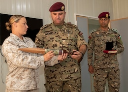 U.S. Marine Corps Capt. Katie Modzelewski (left), with 11th Marine Expeditionary Unit Female Engagement Team (FET), presents a personalized spartan sword to Col. Raaed Dora, with Jordan Armed Forces-Arab Army (JAF), as a gift of appreciation during the closing ceremony of a subject matter expert exchange with the JAF Quick Reaction Force FET August 7, 2019 in Jordan. The U.S. is committed to the security of Jordan and to partnering closely with JAF to meet common security challenges.