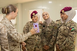 U.S. Marine Cpl. Danielle Grimshaw (left), with 11th Marine Expeditionary Unit (FET), shows members of the Jordan Armed Forces-Arab Army Quick Reaction Force (FET) the selfie they took after the closing ceremony of the subject matter exchange between the two countries August 7, 2019. The U.S. is committed to the security of Jordan and to partnering closely with JAF to meet common security challenges.