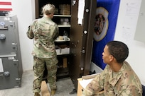 1st Lt. Bridget Auch, 247th Finance Management Support Detachment, removes currency from the vault to fill Spc. D'Are Perry's register at Camp Arifjan, Kuwait, Aug. 19, 2019.