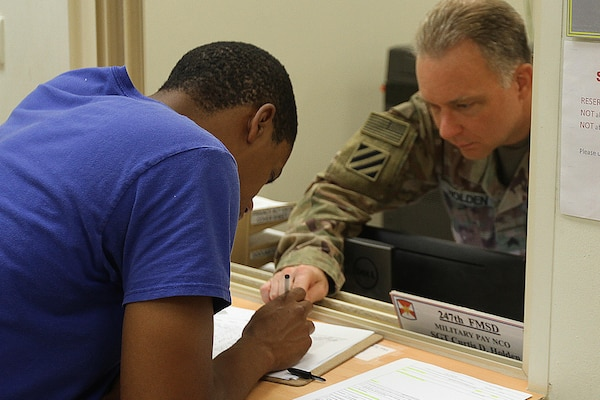 Sgt. Curtis D. Holder, 247th Finance Management Support Detachment, helps with filling out a form, at Camp Arifjan, Kuwait, Aug. 19, 2019.