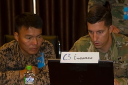Mongolian Army Sgt. Maj. Byambaa Nyambayar, operations engineer non commissioned officer for exercise Regional Cooperation 2019 (RC19), left, and U.S. Army Sgt. 1st Class Paul Brown, operations engineer non commissioned officer for RC19, Massachusetts Army National Guard, discuss training operations during exercise Regional Cooperation 2019 at Dushanbe, Tajikistan, 2019. Exercise Regional Cooperation is an annual exercise to help strengthen military-to-military relationships between the United States and partners in Central and South Asia. The exercise enhances regional security and stability among the participating nations.