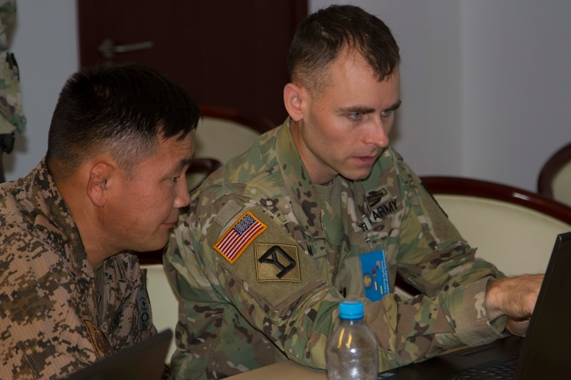 Mongolian Army Maj. Badan Gansukh, engineer officer for exercise Regional Cooperation 2019 (RC19), and U.S. Army Capt. Alan Molin, operations engineer planner for RC19, Massachusetts Army National Guard, discuss training operations during exercise Regional Cooperation 2019 at Dushanbe, Tajikistan, 2019. Exercise Regional Cooperation is an annual exercise to help strengthen military-to-military relationships between the United States and partners in Central and South Asia. The exercise enhances regional security and stability among the participating nations.