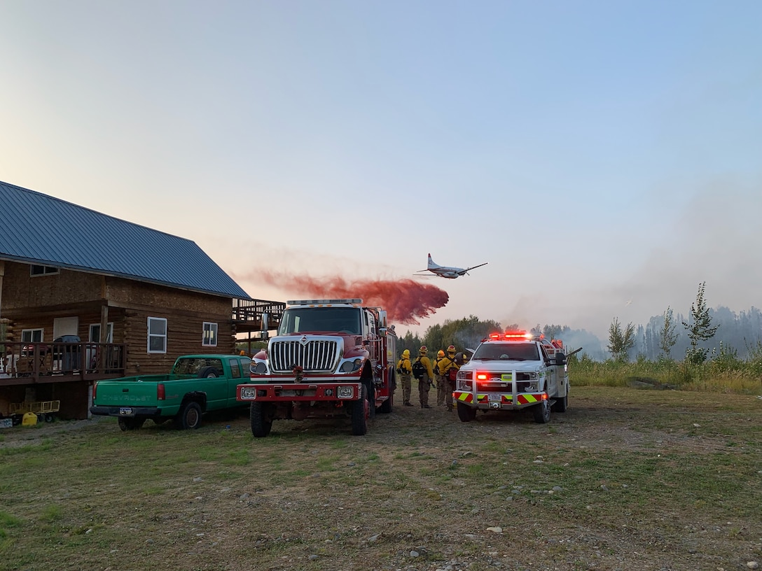 Joint Base Elmendorf-Richardson firefighters wait to re-engage fire suppression efforts while a Candian aircraft drops flame retardant on the McKinley Fire near mile marker 90.5 along the Parks Highway in Alaska, Aug. 18, 2019. The Matanuska-Susitna area fire management officer requested assistance from the JBER taskforce, which immediately responded and fought the fire alongside local and state firefighters.