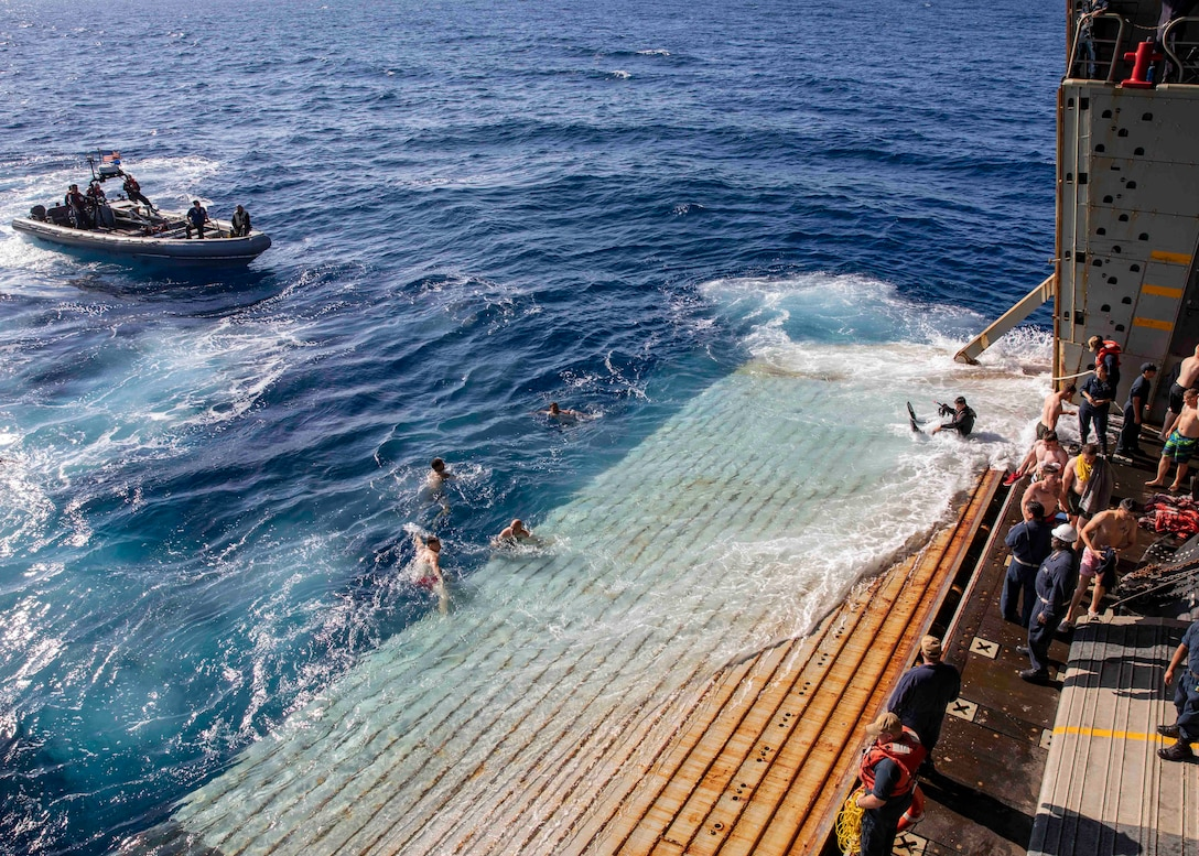 190702-M-QT322-1022 ATLANTIC OCEAN (July 7, 2019) U.S. Marines and Sailors from the 22nd Marine Expeditionary Unit and the San Antonio-class amphibious transport dock ship USS Arlington (LPD 24) participate in a swim call off the stern gate of the Arlington, July 2. The Arlington is making a scheduled deployment as part of the 22nd MEU and the Kearsarge Amphibious Ready Group, in support of maritime security operations, crisis response and theater security cooperation, while also providing a forward Naval and Marine presence. (U.S. Marine Corps photo by Staff Sgt. Andrew Ochoa/Released)