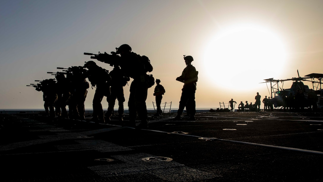 190623-M-QT322-1022 MEDITERRANEAN SEA (June 23, 2019) - U.S. Marines with the 22nd Marine Expeditionary Unit fire service rifles from the flight deck of the San Antonio-class amphibious transport dock ship USS Arlington (LPD 24), during a low-light live-fire range, June 23. The Arlington is making a scheduled deployment as part of the 22nd MEU and the Kearsarge Amphibious Ready Group, in support of maritime security operations, crisis response and theater security cooperation, while also providing a forward Naval and Marine presence. (U.S. Marine Corps photo by Staff Sgt. Andrew Ochoa/Released)