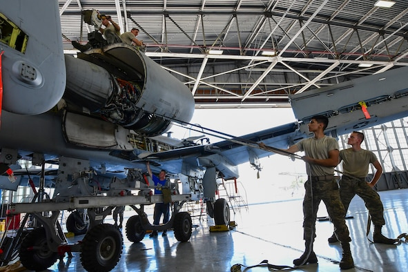 U.S. Air Force Airmen from the 355th Equipment Maintenance Squadron A-10 Phase section work together to remove a TF-34 Turbofan engine from at A-10 Thunderbolt II at Davis-Monthan Air Force Base, Arizona, Aug. 8, 2019. Airmen assigned to the 355th EMS A-10 Phase section are tasked to perform detailed inspections to ensure A-10 Thunderbolt IIs uphold war-ready status. (U.S. Air Force photo by Airman 1st Class Kristine Legate)