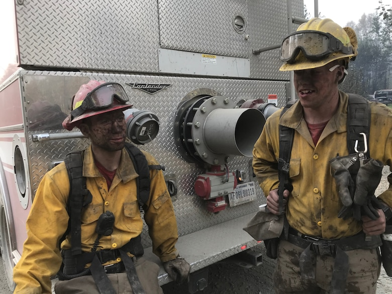 Airmen 1st Class Brody Patterson and Colin Saumier, firefighters with the 673d Civil Engineer Squadron Fire and Emergency Services Flight, take a break from suppression efforts fighting the McKinley Fire near mile marker 90 along the Parks Highway in Alaska, Aug. 19, 2019. The Matanuska-Susitna area fire management officer requested assistance from the JBER taskforce, which immediately responded and fought the fire alongside local and state firefighters.
