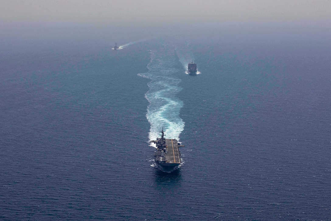 190507-N-YH603-1236 STRAIT OF HORMUZ (May 7, 2019) The Wasp-class amphibious assault ship USS Kearsarge (LHD 3), center, the dry cargo and ammunition ship USNS Alan Shepard (T-AKE 3), right, and the Arleigh Burke-class guided-missile destroyer USS McFaul (DDG 74) transit the Strait of Hormuz. Kearsarge is the flagship for the Kearsarge Amphibious Ready Group and, with the embarked 22nd Marine Expeditionary Unit, is deployed to the U.S. 5th Fleet area of operations in support of naval operations to ensure maritime stability and security in the Central Region, connecting the Mediterranean and the Pacific through the western Indian Ocean and three strategic choke points. (U.S. Navy photo by Mass Communication Specialist 2nd Class Casey Moore/Released)