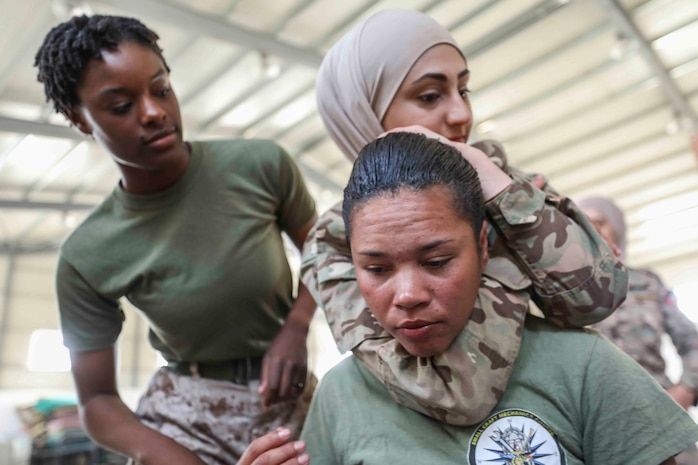 A Jordan Armed Forces-Arab Army soldier executes a figure four variation choke technique on Sgt. Nicole Turner, a heavy equipment mechanic, as a part of Marine Corps Martial Arts Program training with the 22nd Marine Expeditionary Unit's female engagement team, April 25, 2019.
