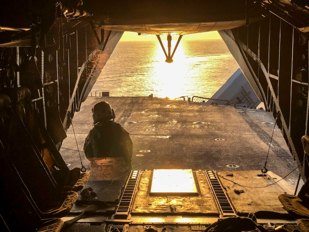 A U.S. Marine with the 22nd Marine Expeditionary Unit observes the sunrise from the back of a CH-53E Super Stallion prior to departure from the Wasp-class amphibious assault ship USS Kearsarge (LHD-3) March 29, 2019.