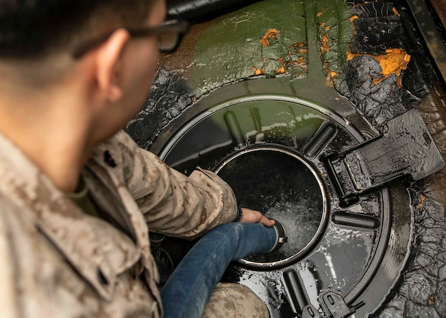 .S. Marine Cpl. Carlos Escobedo, a water support specialist with the 22nd Marine Expeditionary Unit, fills a container with water on a Medium Tactical Vehicle Replacement in the well deck of the Wasp-class amphibious assault ship USS Kearsarge (LHD-3) March 12, 2019.
