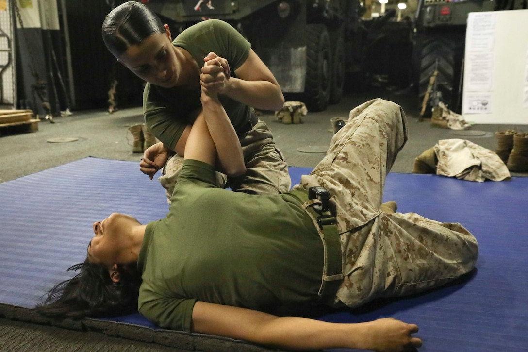 190304-M-YD783-1024 GULF OF OMAN (MARCH 4, 2019) U.S. Marine Cpl. Elizabed Angel, left, a motor transport mechanic with the 22nd Marine Expeditionary Unit, reacts as Sgt. Brittnay Warf, right, a wrecker operator also with the 22nd MEU, exectues the counter–to-the-mount technique on her during Female Engagement Team training in the well deck of the Wasp-class amphibious assault ship USS Kearsarge (LHD-3). FET Marines conducted the Marine Corps Martial Arts Program training to build and sharpen their skills in preparation for teaching troops from foreign military. Marines and Sailors with the 22nd MEU and Kearsarge Amphibious Ready Group are deployed to the 5th Fleet area of operations in support of naval operations to ensure maritime stability and security in the Central Region, connecting the Mediterranean and the Pacific through the western Indian Ocean and three strategic choke points. (U.S. Marine Corps photo by Lance Cpl. Tawanya Norwood/Released)