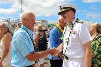 Capt. Greg Burton, shipyard commander, welcomes Mayor Kirk Caldwell to Dry Dock One for its 100th centennial celebration.