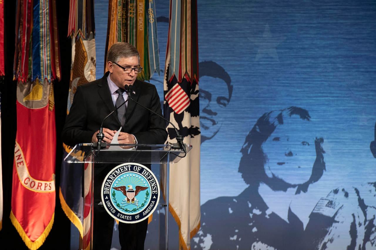 A man stands behind a lectern that bears the seal of the Department of Defense. Behind him are four military flags.