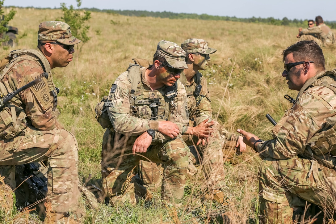 Four soldiers kneel in a field and talk.